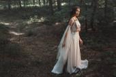 elegante mystische Elfe im Kleid mit Blumen, die im Wald spazieren gehen