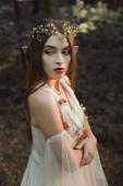 gyönyörű női elf virág ruha és koszorú álló erdő keresztezett karokkal