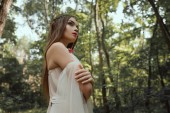 Photo elegant mystic elf in dress standing with crossed arms in forest