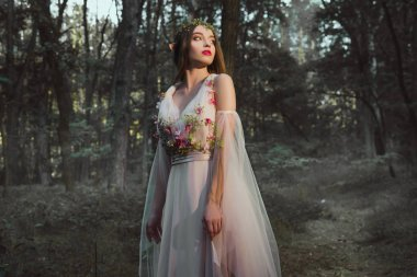 attractive mystic girl with elf ears posing in flower dress in forest