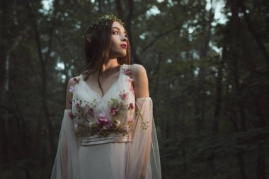 attractive mystic elf in elegant dress with flowers in forest