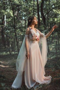 mystic elf in character in flower dress walking in woods