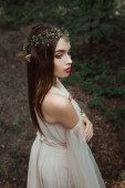 Photo mystic elf in elegant dress and floral wreath in forest