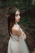mystische Elfe in elegantem Kleid und floralem Kranz im Wald