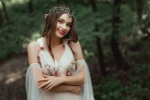 Photo attractive smiling girl in dress and floral wreath posing in woods