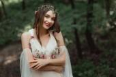 vonzó mosolygó lány ruha és jelentő erdőben Virág Koszorú