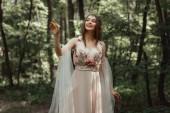 Happy elf lány elegáns ruha virágok erdőben