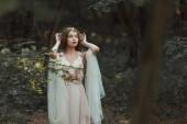 Fantasie-Mädchen mit Elfenohren im Blumenkleid posiert im Wald
