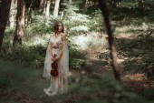 Photo mystic elf in elegant dress holding violin in beautiful forest