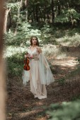 Photo attractive mystic elf in elegant dress holding violin in beautiful forest