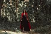 misztikus lány fekete ruha és piros köpenyt, séta az erdő