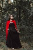 atraktivní mystic žena v černých šatech a červený plášť, který v lese