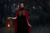 elegáns misztikus lány piros köpenyt, petróleumlámpa, séta a sötét erdőben