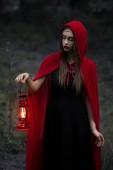 Fényképek gyönyörű misztikus lány séta a sötét erdőben, a petróleumlámpa piros köpeny