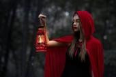 Mystic dívka procházky v temném lese se petrolejové lampy