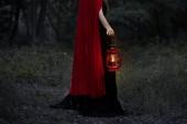 oříznutý pohled mystické dívky s petrolejové lampy v temném lese