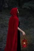 Mystic dívka v červené pláštěnce chůze v temném lese se petrolejové lampy