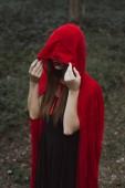 Fotografie mystic woman in red cloak and hood in dark woods
