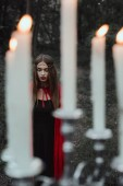 selective focus of mystic girl and candelabrum with flaming candles on foreground