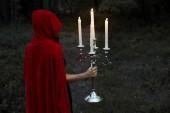 Mystic dívka v červený plášť, který drží svícen s hořící svíčky v temném lese