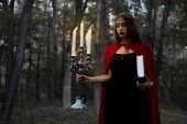 Fotografie mystic girl in red cloak holding candelabrum with flaming candles and magic book in dark woods