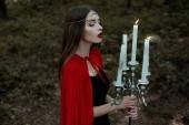 elegáns misztikus lány piros köpenyt és fúj gyertya, gyertyatartó, sötét erdő koszorú