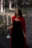 gyönyörű magic girl gazdaság lángoló gyertya, gyertyatartó, erdőben