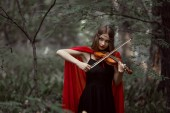 Fotografie attractive mystic girl in red cloak playing on violin in forest