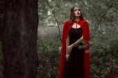 Photo attractive mystic girl in red cloak in forest