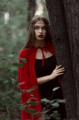 Photo beautiful mystic girl in red cloak and elegant wreath in forest