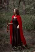 atraktivní mystic žena v červené plášti držící housle v temném lese
