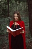 gyönyörű misztikus lány piros köpenyt és koszorú mágia olvasókönyv erdőben