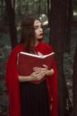 misztikus gyönyörű lány piros köpenye és a gazdaság magic könyv, erdő koszorú