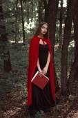 krásná dívka v červené pláštěnce s magií rezervovat v lese