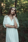 Fotografie attractive young woman posing in stylish dress and floral wreath in forest