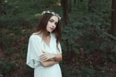 Fotografia bella ragazza tenera che propone in vestito bianco e corona floreale nella foresta