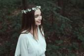 elegante ragazza sorridente che posa in vestito bianco e corona floreale nei boschi