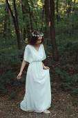 Fotografia dolce bella ragazza in vestito bianco che cammina nella foresta