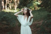 Photo tender girl with closed eyes posing in floral wreath in forest