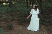 ragazza elegante in vestito bianco e corona floreale camminando nel bosco