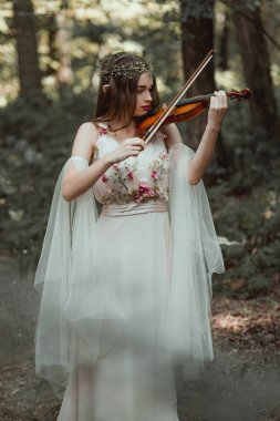 beautiful mystic elf playing violin in forest