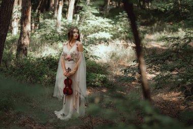 mystic elf in elegant dress holding violin in beautiful forest