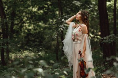 mystic elf character in flower dress holding violin in green forest