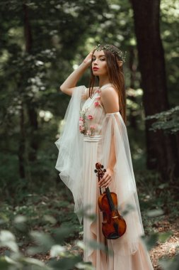mystic elf in flower dress and floral wreath holding violin in forest