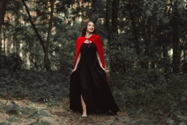 Beautiful mystic girl in black dress and red cloak walking in forest stock vector