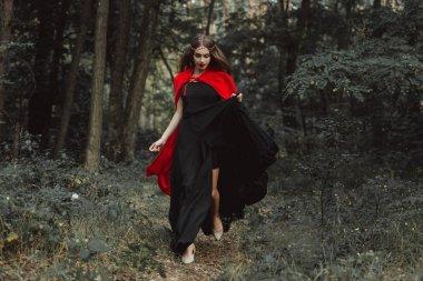 Elegant mystic girl in black dress and red cloak running in woods stock vector