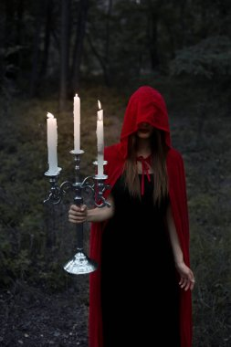 magic woman in red cloak and hood holding candelabrum with candles in dark forest