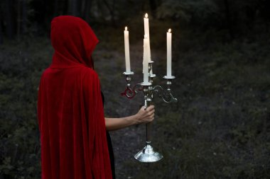mystic girl in red cloak holding candelabrum with flaming candles in dark woods