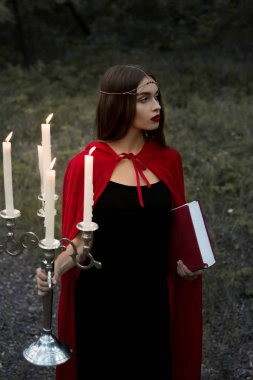 beautiful mystic girl in red cloak holding candelabrum with flaming candles and magic book in forest