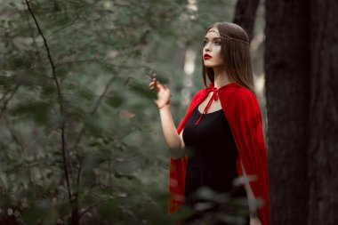 mystic young woman in red cloak in forest
